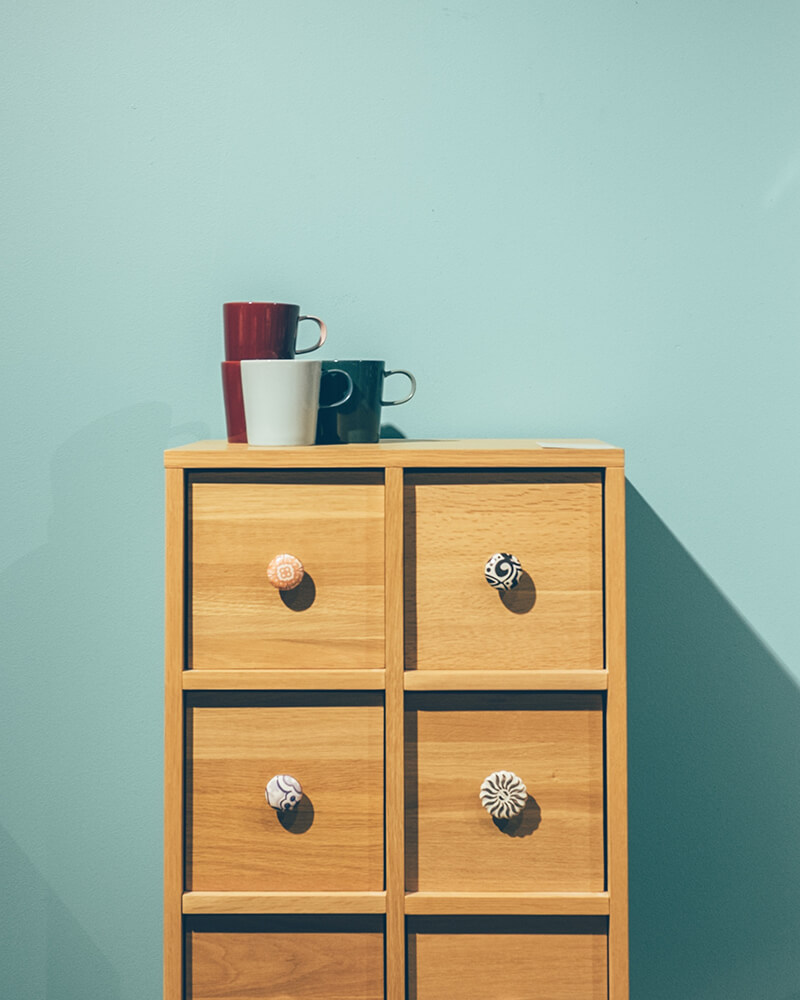chest of wooden drawers with teacups on top